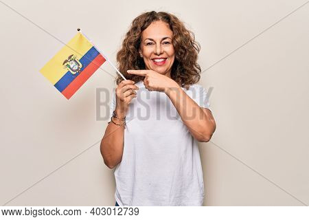 Middle age beautiful patriotic woman holding colombian flag over isolated white background smiling happy pointing with hand and finger