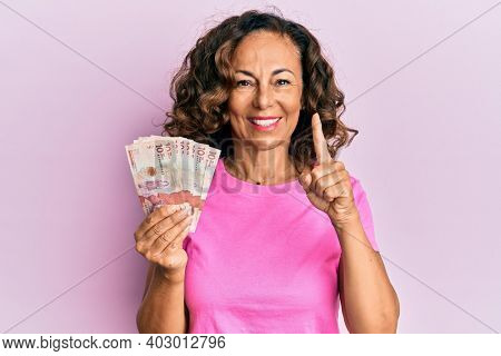Middle age hispanic woman holding 10 colombian pesos banknotes smiling with an idea or question pointing finger with happy face, number one