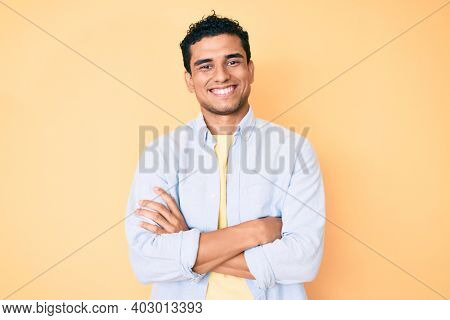 Young handsome hispanic man standing over yellow background happy face smiling with crossed arms looking at the camera. positive person.