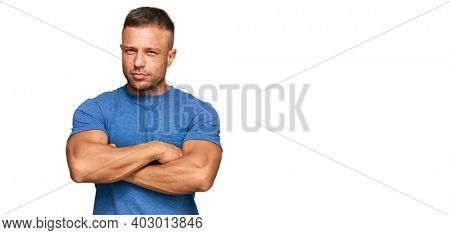 Handsome muscle man wearing casual clothes skeptic and nervous, disapproving expression on face with crossed arms. negative person.