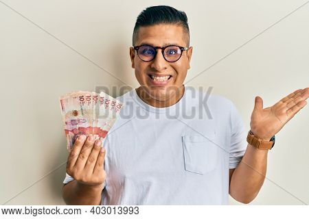 Young latin man holding 10 colombian pesos banknotes celebrating achievement with happy smile and winner expression with raised hand