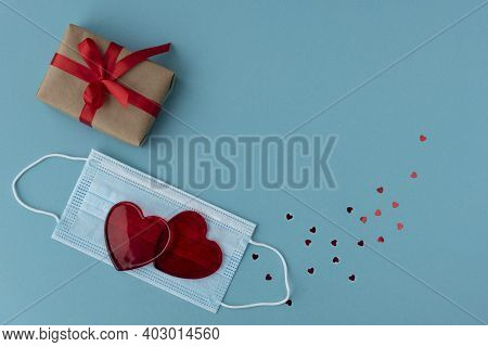 Two Red Heart Lie On Protective Medical Mask, Wrapped Giftbox And Little Sparkling Heart Confetti Ar