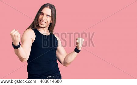 Young adult man with long hair wearing rocker style with black clothes and contact lenses screaming proud, celebrating victory and success very excited with raised arms