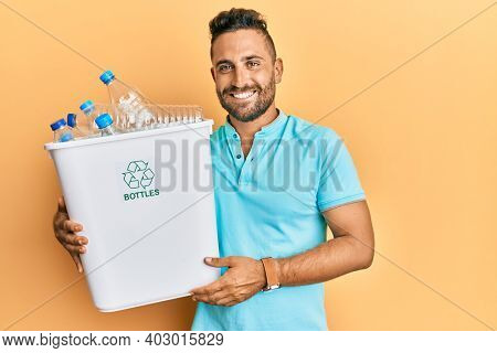 Handsome man with beard holding recycling wastebasket with plastic bottles looking positive and happy standing and smiling with a confident smile showing teeth