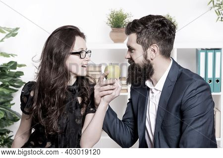 Apple Is High In Vitamin. Boss And Sensual Secretary Holding Vitamin Fruit In Office. Bearded Man An