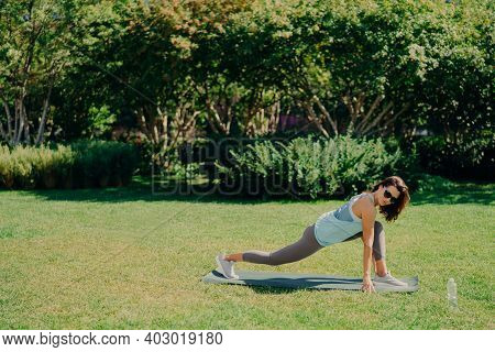 Outdoor Sport Concept. Healthy Fit Energetic Young Woman Does Fitness Exercises On Fitness Mat Dress