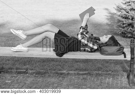 Reading Is Fun. Happy Child Read Book Lying On Park Bench. School Library. Imagination And Fantasy.