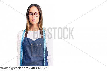 Beautiful brunette young woman dressmaker designer wearing atelier apron with serious expression on face. simple and natural looking at the camera.