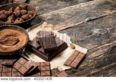 Chocolate Bars With Truffles And Cocoa Powder. On A Wooden Background.