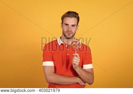 Cant Wait To Get A Bite Of Lollipop. Young Guy Hold Lollipop Yellow Background. Eating Lollipop. Lar