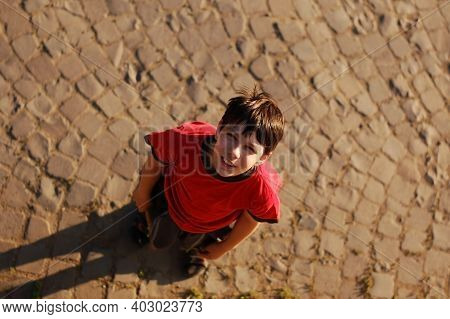 A Boy In A Red T-shirt Walks In The City At Sunset. He Raised His Head And Looked Up. Top View. He H