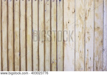 A Simple Wooden Fence Is Made Of Various Wooden Boards. Wooden Texture, Background. Horizontal