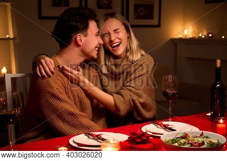 Happy Young Couple In Love Hugging, Laughing, Drinking Wine, Enjoying Talking, Having Fun Together C