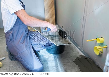 Ceramic Wood Effect Tiles. A Male Tiler Applies Mortar To The Back Of Ceramic Tiles To Install Porce