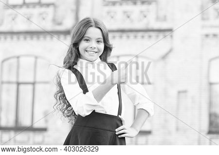 Fashion And Beauty. Girl Has Curly Hair. Little Girl In Classy Uniform Pointing Finger. Back To Scho
