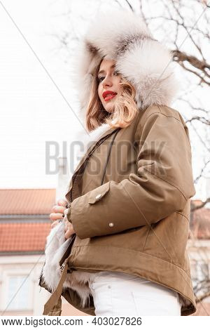 Stylish Girl In A Down Jacket With A Hood On Her Head. Young Woman With Red Lips. Outdoor Portrait O