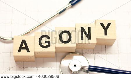 Agony Word Written On Wooden Blocks And Stethoscope On Light White Background