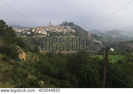 Panoramic view at a foggy morning in the hills of Polop de Marina with church and castell over green forest at the Costa Blanca, Spain