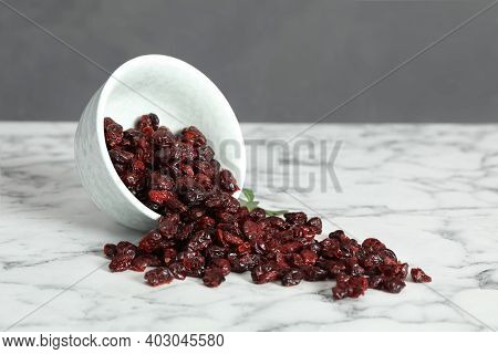 Overturned Bowl With Tasty Dried Cranberries On White Marble Table