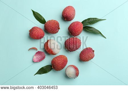Fresh Ripe Lychees With Leaves On Turquoise Background, Flat Lay