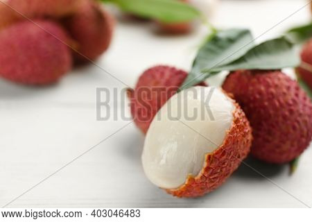 Fresh Ripe Lychees With Leaves On White Wooden Table, Closeup. Space For Text