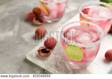 Lychee Cocktail With Lime And Ice On Grey Table, Space For Text
