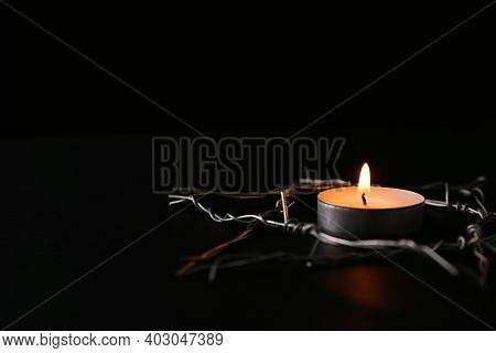 Burning Candle And Star Of David Made With Barbed Wire On Black Background, Space For Text. Holocaus