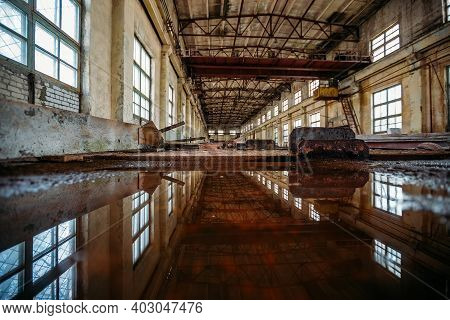 Inside Of Flooded Dirty Abandoned Ruined Industrial Building With Water Reflection