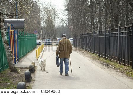 The Old Man Walks Down The Street. An Elderly Man With A Stick Walks Forward. Grandpa Is Walking The