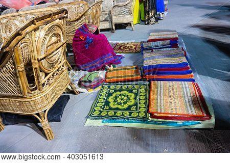 Resting Woman Seller Displaying Woolen Carpets , Door Mats, Handicraft Products. At Hastashilpomela