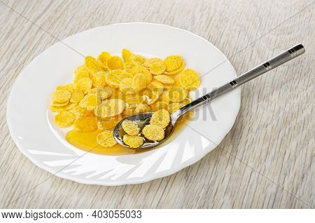 Teaspoon In White Plate With Corn Flakes And Liquid Honey On Wooden Table