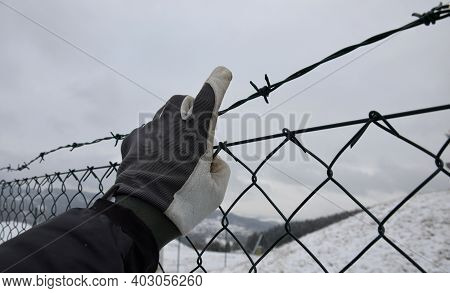 Protesting Man In Gray Tactical Gloves Overcome A Barbed Wire Fence And Get Behind A Wire Fence. Sho