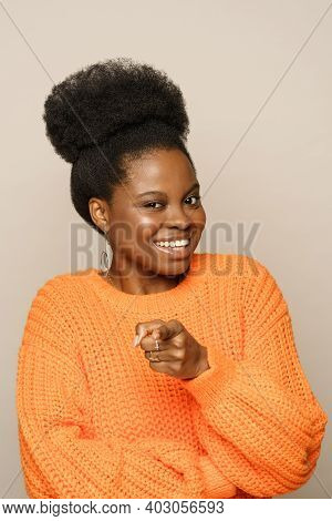Hey, You. Cheerful Positive Young Afro American Woman With Curly Hair Wear Orange Jumper In Good Moo