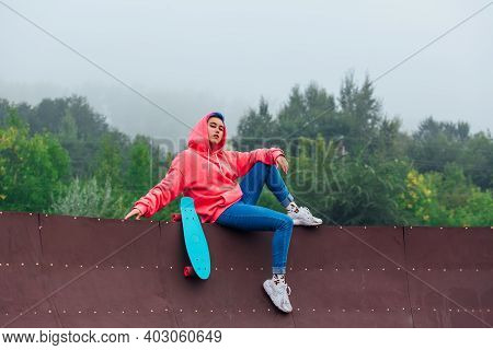 Summer Lifestyle Image Of Trendy Pretty Young Girl Sitting Next To The Skateboard Court With Her Pla