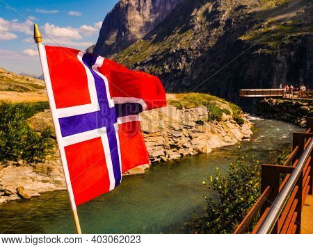 Trollstigen Mountain Road Landscape In Norway, Europe. Norwegian Flag Waving And Many Tourists Peopl