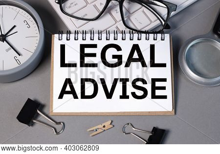 Legal Advise. Text On White Paper On Gray Background. Glasses. Alarm Clock. Magnifier