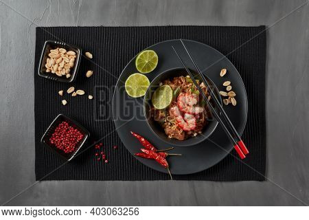 Pad Thai. Stir-fried rice noodles with chicken meat, shrimps,  scrambled egg, peanuts, vegetables and sauce in bowl on gray slate background. Top view. Thai food. Setting table