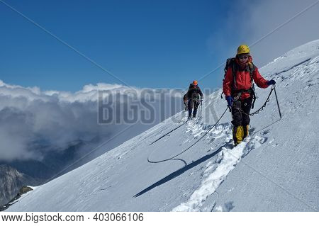 Bunch Of Mountaineers Climbs Or Alpinists To The Top Of A Snow-capped Mountain