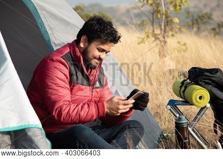 Happy Smiling Young Traveler Busy Using Mobile Phone From Camping Tent - Concept Of Digital Nomadic