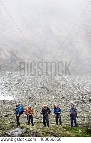 Grop Of Male Hikers Holding Trekking Sticks And Looking At Camera While Standing On Grassy Hillside.