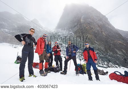 Group Of Male Hikers In Sunglasses Standing On Snow Covered Filed At The Bottom Of Mountain Looking