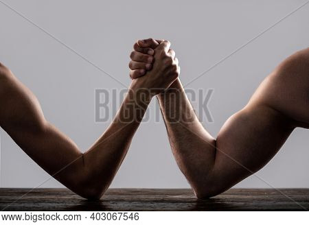 Arm Wrestling. Heavily Muscled Man Arm Wrestling A Puny Weak Man. Arms Wrestling Thin Hand And A Big