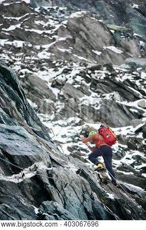 Male Alpinist With Backpack Using Rope While Climbing Alpine Ridge. Young Traveler Ascending Mountai