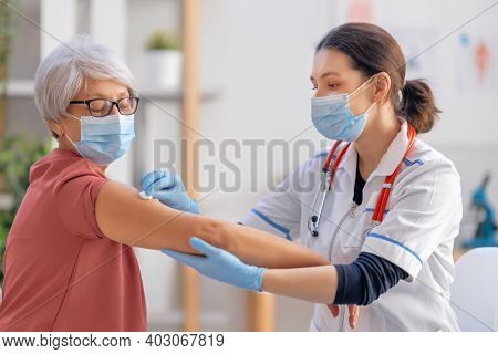 Doctor giving a senior woman a vaccination. Virus protection. COVID-2019.