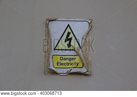 Electric Danger Symbol With A Words Danger Electricity. Sticker Is Old And Peeled Off And Burnt-out