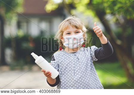 Little Toddler Girl In Medical Mask As Protection Against Pandemic Coronavirus Quarantine Disease. C