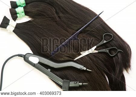 A Large Strand Of Hair With A Thin Comb-scissors Device For Encapsulating On A White Background. Hig