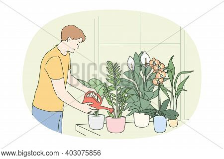 Houseplants And Home Gardening Concept. Young Smiling Man Watering Green Home Plants And Flowers In