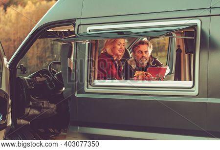 Caucasian Couple Watching Movie Online Inside Their Modern Camper Van During Their Weekend Getaway.