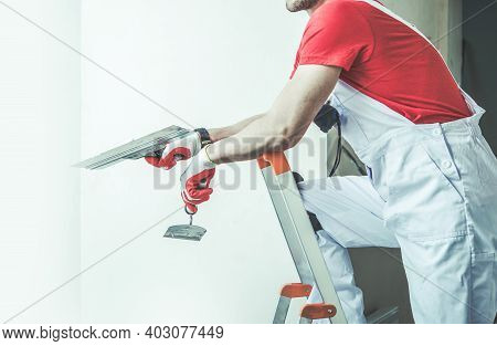 Caucasian Worker In His 30s With Patching Tools In His Hand. Drywall Patch And Preparing Interior Ap